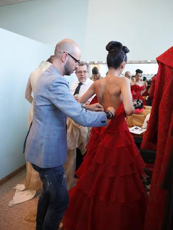 Vistiendo a una modelo bajo la atenta mirada del creador sevillano. Desfile de Alta Costura de Petro Valverde.